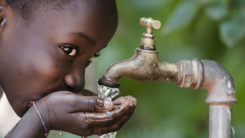 Girl drinking water from a tap