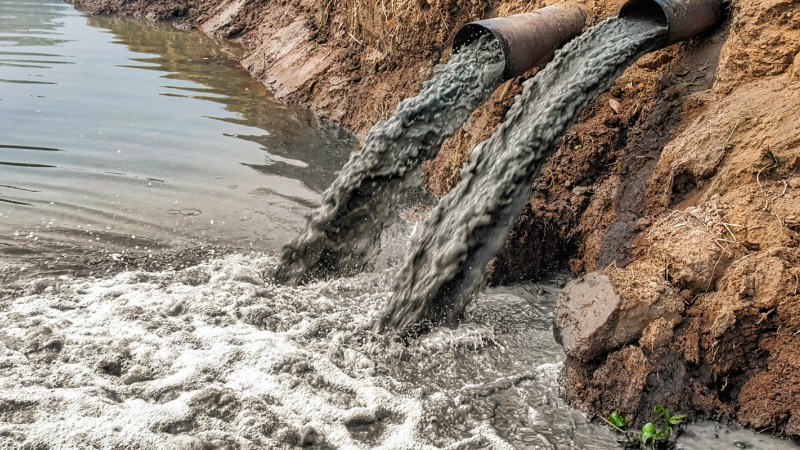 Pipes pumping polluted water into a river