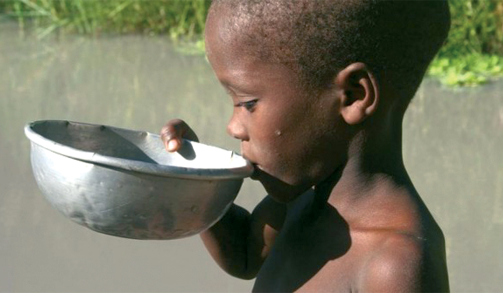 Kid drinking from a metal bowl